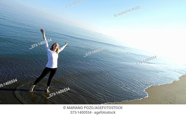 Young woman doing yoga in a mediterranean beach