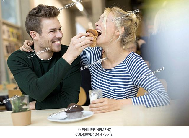 Mid adult man feeding muffin to girlfriend in cafe