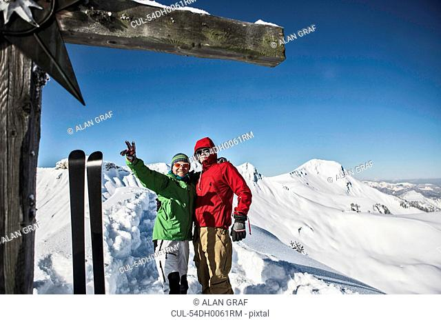 Hikers posing on snowy mountaintop