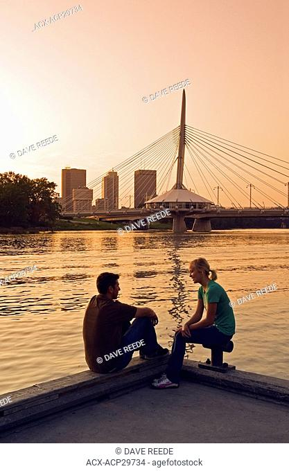 couple on dock along the Red River with Winnipeg skyline in the background, Manitoba, Canada