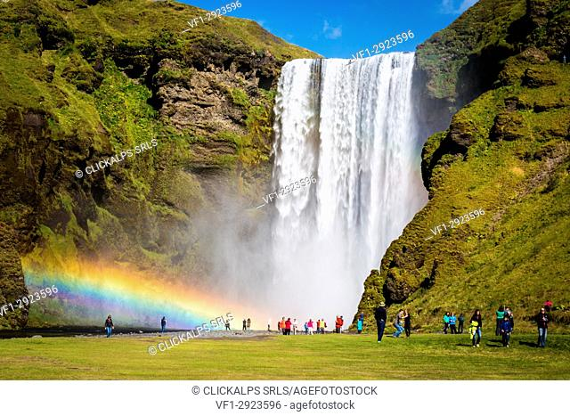 Iceland, Skogafoss waterfall with double rainbow and tourist admiring the natural wonder