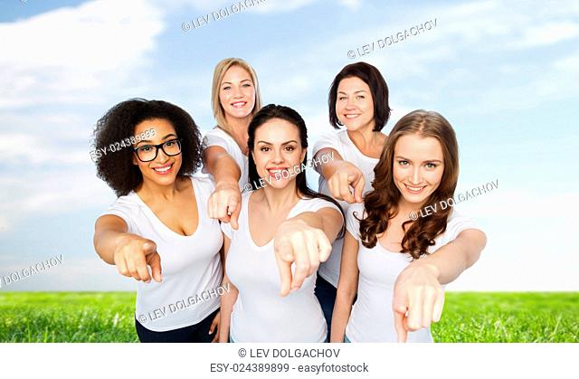 choice, friendship, body positive, gesture and people concept - group of happy different size women in white t-shirts pointing finger on you over blue sky and...