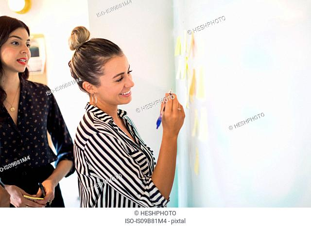 Young businesswoman writing on whiteboard adhesive notes