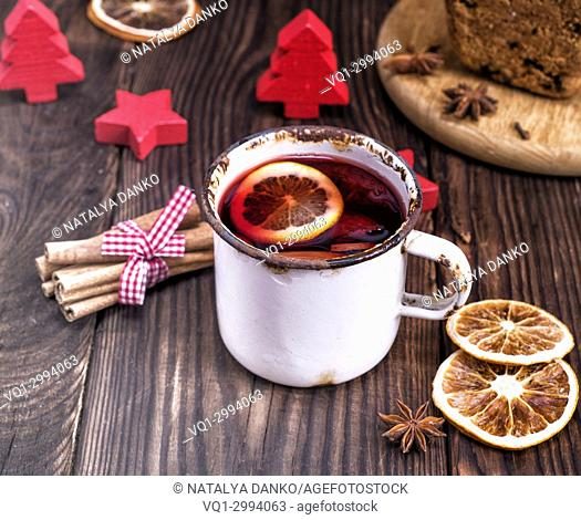 mulled wine in a white iron mug on a brown wooden table
