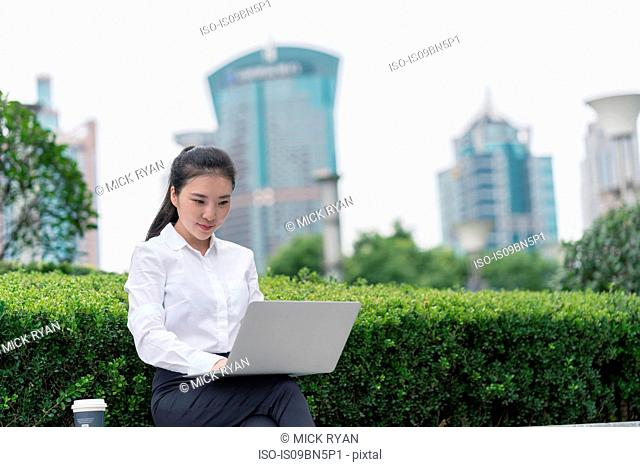 Young businesswoman typing on laptop in city financial district, Shanghai, China