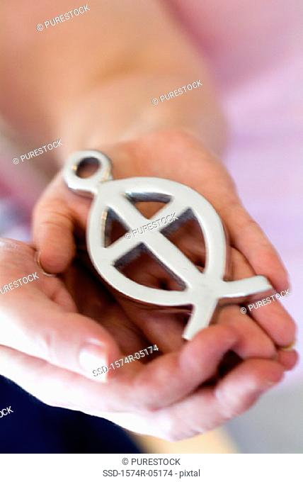 Close-up of a person holding an ichthus fish symbol