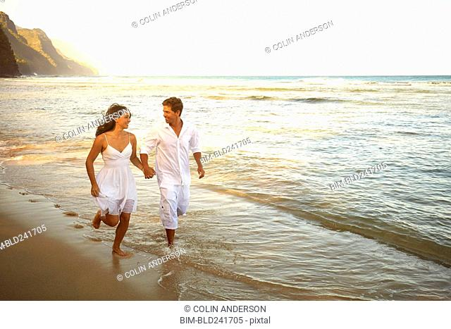 Couple running in ocean waves on sunny beach