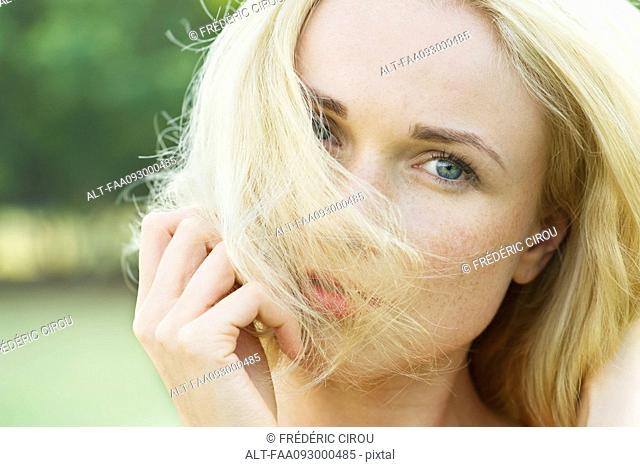 Woman covering face with hair, portrait
