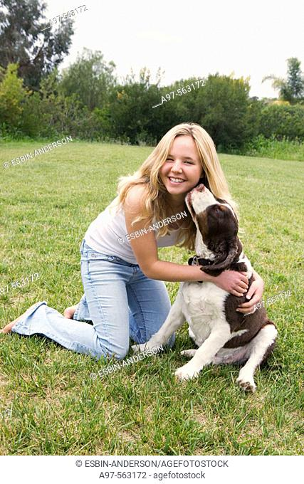 Smiling blonde teen girl in blue jeans and white tank top kneeling on grass lawn, get's a kiss from her pet dog
