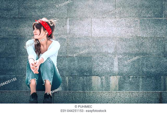 Beautiful girl in jeans and a white T-shirt with a red armband on the head, against the wall background, the concept of urban clothing and youth style