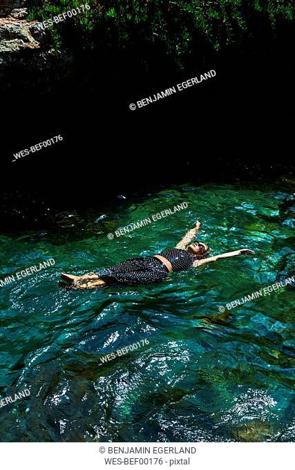Greece, Crete, Hersonissos, woman in dress floating in sea