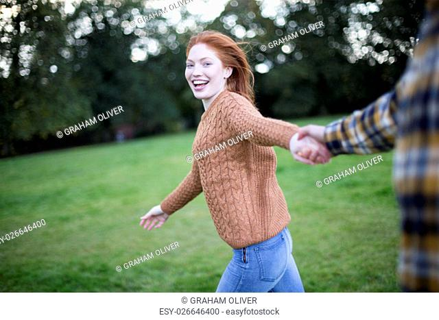 Point of view shot of a young woman running whilst holding her partners hand. She is looking at the camera