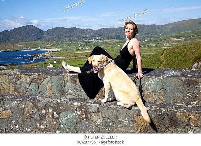 A woman and her dog sit on a stone wall near allihies, county cork ireland