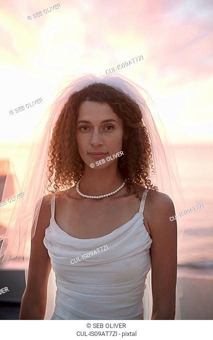 Bride standing on beach against sunset