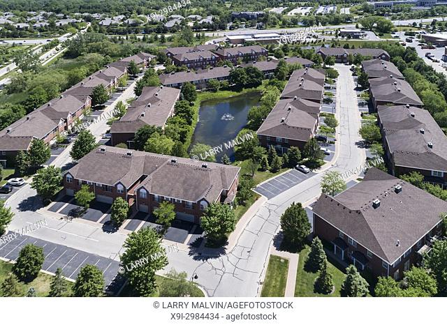 Aerial view of a townhouse complex with a small pond in a Chicago suburban neighborhood of Northbrook, IL in summer. USA