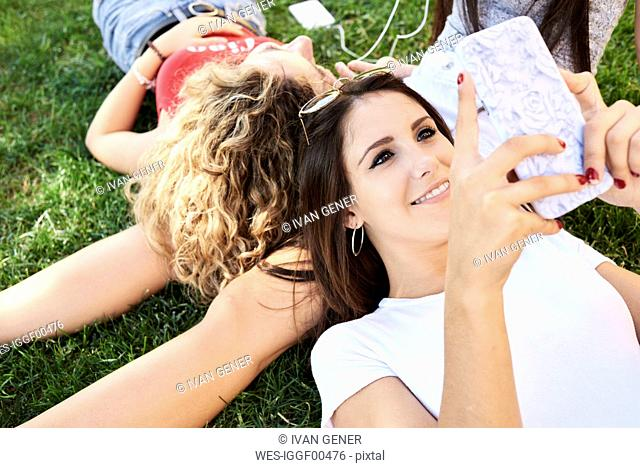 Young woman lying in grass with friends using cell phone