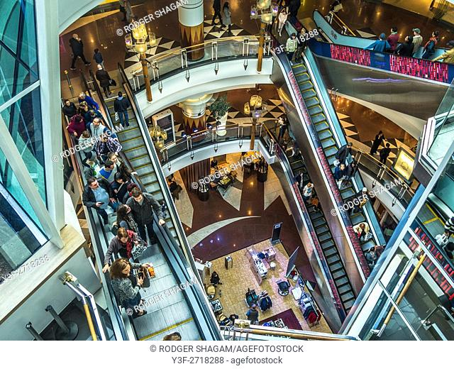 Looking down at banks of escalators in a busy retail shopping mall. Cape Town, South Africa