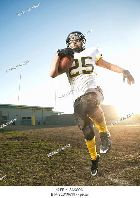 Hispanic football player running with football