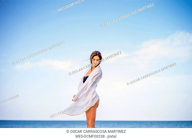 Beautiful young woman wrapped in a towel on the beach
