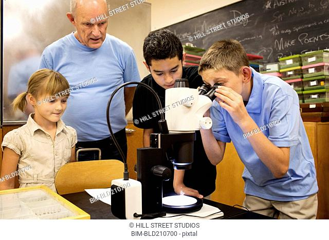 Teacher and students using microscope in laboratory