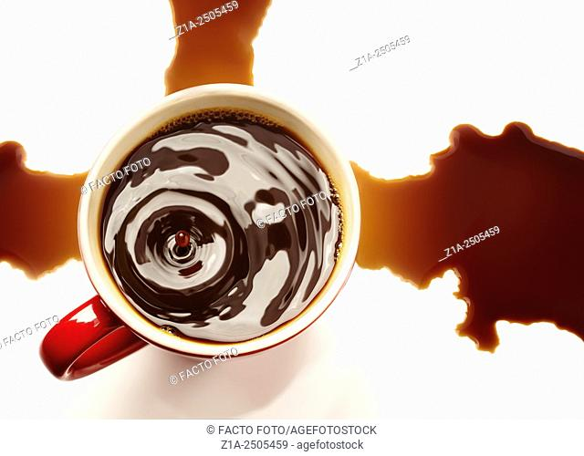 Top view of a drop falling on a red cup of black coffee with a stain on a white background