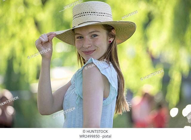 Portrait of happy Hispanic teen girl wearing sunhat in a park