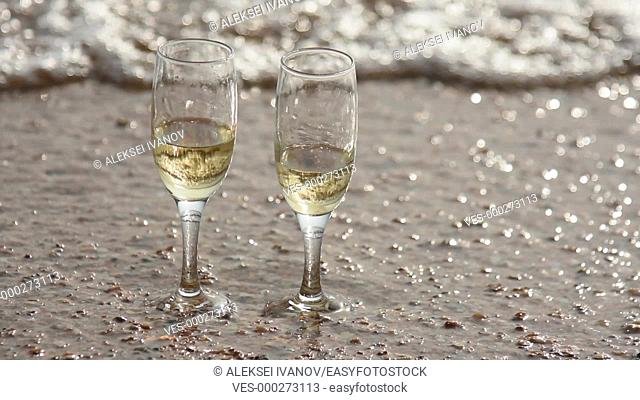 Wave washed away one of two glasses of champagne, standing on the sand on the beach