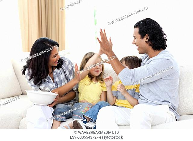 Joyful family watching TV on sofa in the living room