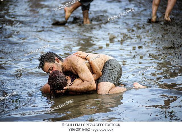 A couple kissing in a mud pool of the Przystanek Woodstock music festival, Kostrzyn, Poland