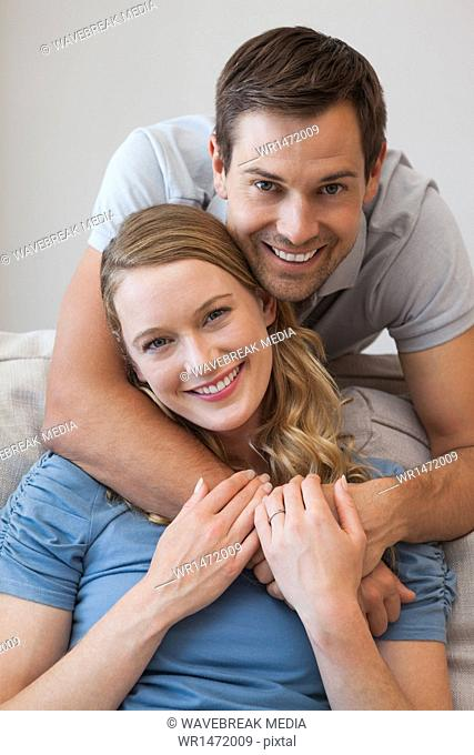 Young man embracing woman from behind at home