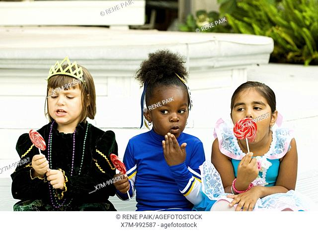 Little girls Asian Indian, black & caucasian dressed in Halloween costumes enjoy their lollipops as one gets caught red-handed eating candy