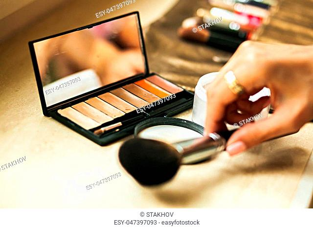 Multi-color powder-case palette with mirror and hand with brush
