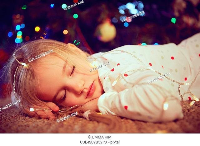 Girl wearing lights asleep on floor at christmas