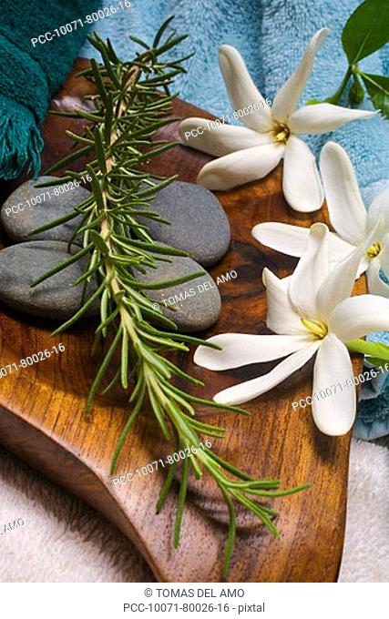 Spa elements, flowers, grey stones and a sprig of rosemary ona wooden platter with towels surrounding