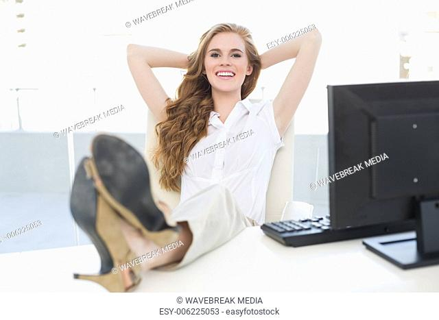 Relaxed businesswoman with legs on desk in office