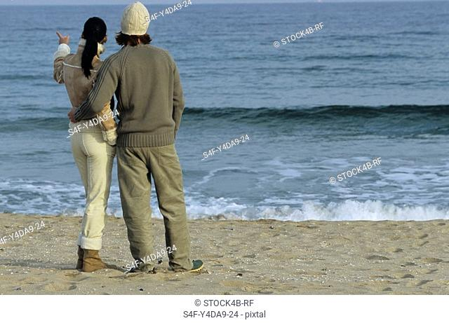 Young auburn-haired Man holding a brownhaired young Woman to his Arm - Love - Togetherness - Beach