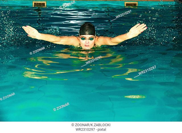 Woman athlete swimming butterfly stroke in pool