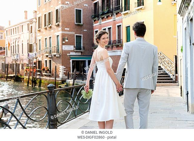 Italy, Venice, happy bridal couple walking hand in hand