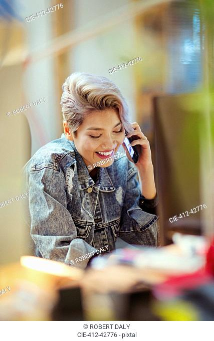 Smiling young woman talking on smart phone