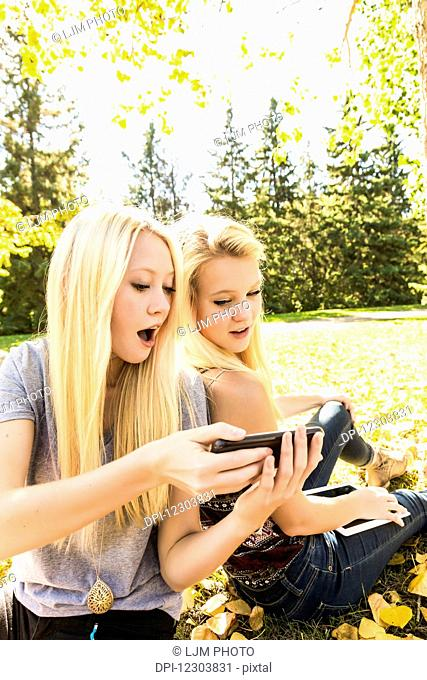 Two sisters having fun outdoors in a city park and looking at social media on their smart phone and tablet; Edmonton, Alberta, Canada