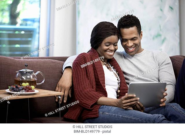 Couple sitting on sofa using digital tablet together