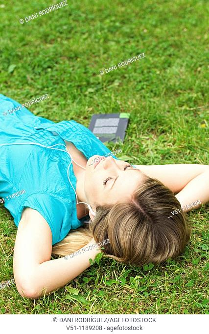 Young woman blonde woman lying down on the park relaxing