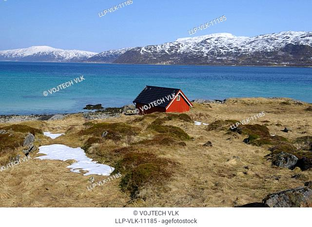 The red wooden little house on rock seacoast and snowy mountains on background
