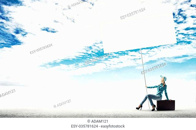 Beautiful woman traveler in hat with blank banner sitting on her retro suitcase
