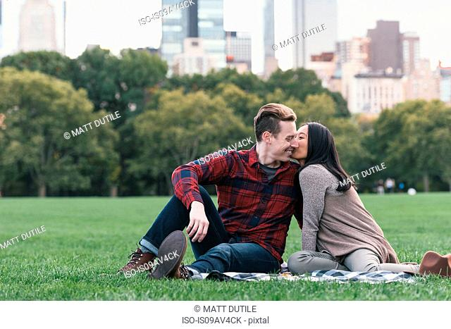Romantic mid adult couple on picnic blanket in Central Park, New York, USA