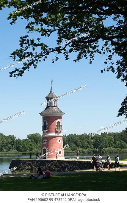 02 June 2019, Saxony, Moritzburg: Passers-by walk along a pier in front of the inland lighthouse. Photo: Sebastian Kahnert/dpa-Zentralbild/dpa