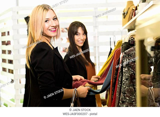 Young women in fashion boutique shopping for clothes