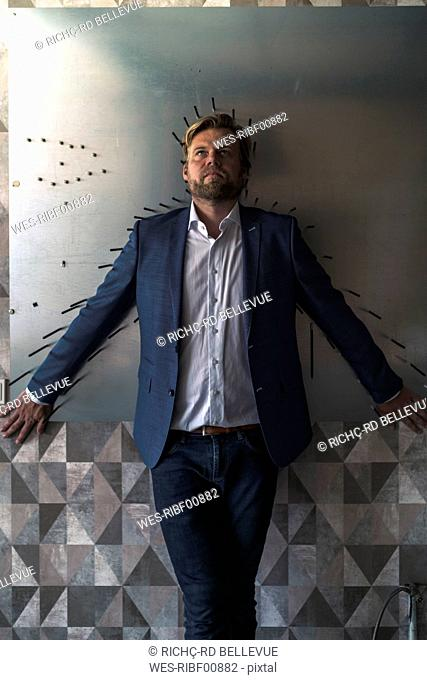Businessman standiing in boardroom with back to a magnet wall, framed by arrows