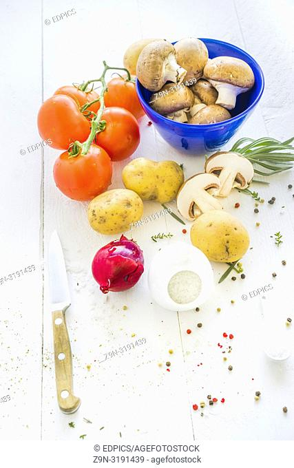 white tabletop displaying brown portobello mushrooms in a blue bowl, tomatoes, potatoes, a red onion, herbs and coarse sea salt and red, green