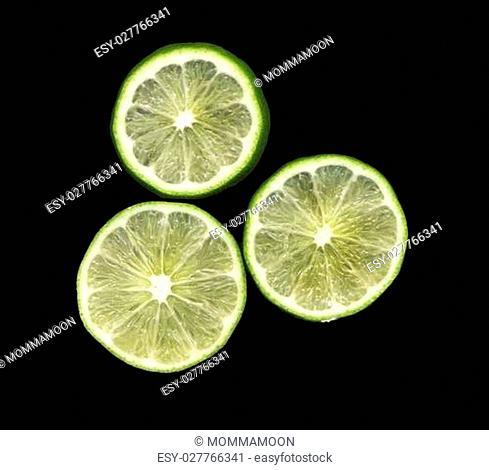 Three lime slices on black backdrop